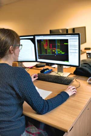Jonge vrouw die in kantoor op computer werkt. Vrouwelijke architect in glazen ontwerp gebouw