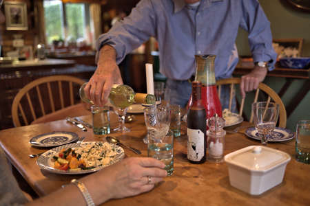Man in blue shirt  pouring white wine to glass during dinner in house. Posh home interior with homey atmosphere at lunch