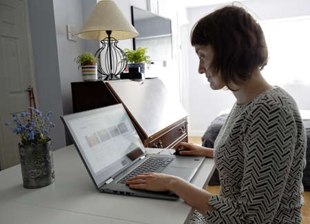 Young woman check news in home office on laptop computer. Female lady browsing and reads interesting website