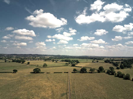 Aerial view on cheshire plains and fields. Summer sky with white clouds