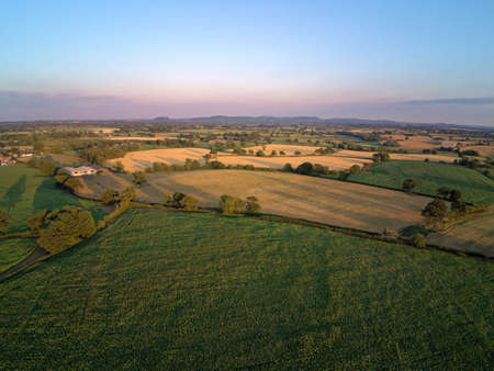 Aerial view on cheshire plains and fields. Summer pink sunset Standard-Bild