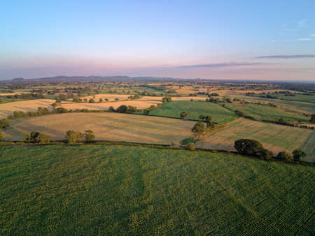 Aerial view on cheshire plains and fields. Summer sunset behind