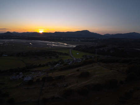 Aerial view, Drone panorama sunset over mountains, sea, Snowdonia in background in North Wales