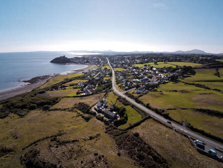 Aerial view, Drone panorama of sea with silhouette of Criccieth castle and village in background Standard-Bild