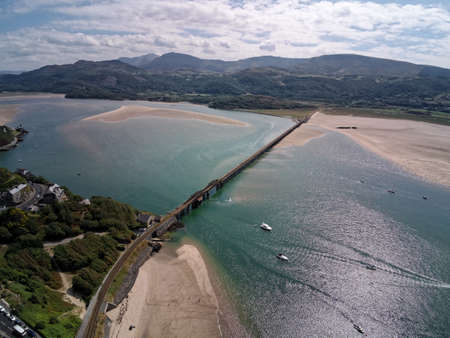 Aerial view, Drone panorama over rising tide sea, bay, anchored boats, steel railway bridge in Barmouth, Wales