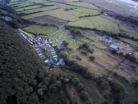 Aerial view, Drone panorama golden hour sunset over Barcdy touring caravan and camping tent park in Wales
