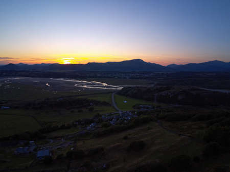 Aerial view, Drone panorama colorful sunset over hills, sea, Snowdonia mountains in background in North Wales Standard-Bild