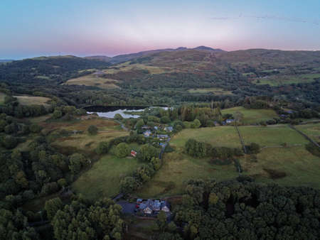 Aerial view, Drone panorama golden hour sunset over hills, Snowdonia mountains in background in North Wales