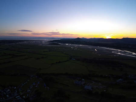 Aerial view, Drone panorama golden hour sunset over hills, sea, Snowdonia mountains in background in North Wales