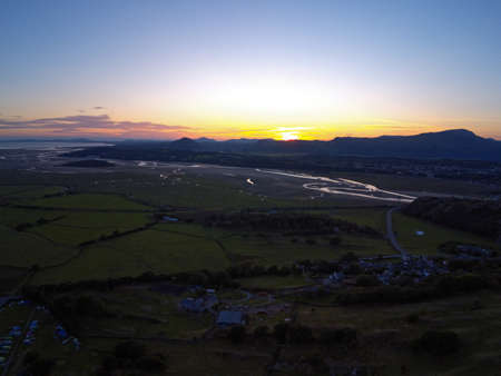Aerial view, Drone panorama sunset over Talsarnau village hills, Snowdonia mountains in background in North Wales