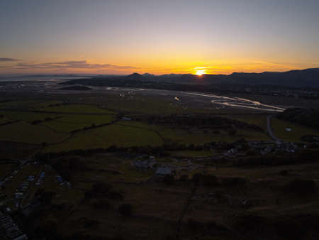 Aerial view, Drone panorama sunset over hills, sea, Snowdonia mountains in background in North Wales Standard-Bild