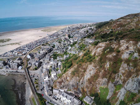 Aerial view, Drone panorama over buildings, railway line, road, beach and old town of Barmouth, Wales