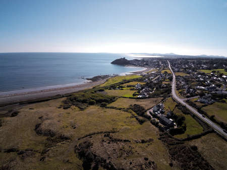 Aerial view, Drone panorama of sea with silhouette of Criccieth castle and town in background