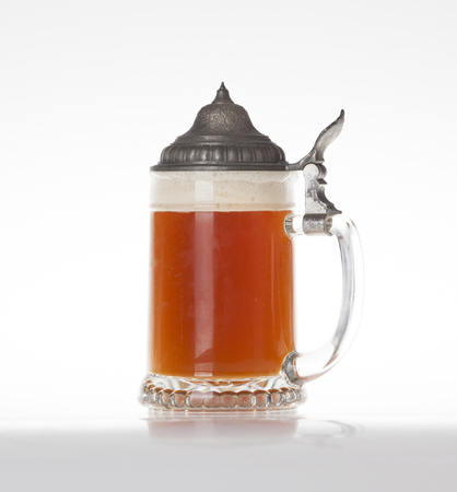 stein: Beer stein filled with wheat beer on a light table with closed metal lid Stock Photo