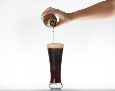 schwarzbier: Gie�en dunkles Bier in ein Glas auf einem isolierten Hintergrund