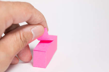 notepaper: Hand pulling notepaper sticker Stock Photo