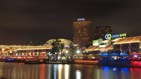 SINGAPORE - MARCH 02: Night shot of Clarke Quay at late evening and night over river in Singapore. Illuminated building of popular meeting place. At left side in background are hotels. In restaurants at promenade are many people. Editorial