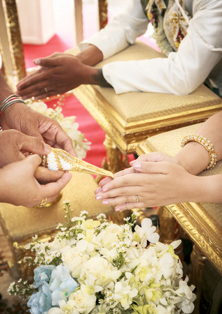 Hands pouring blessing water into brides bands , Thai Wedding Ceremony Stock Photo