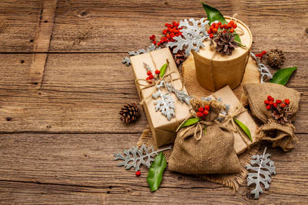 Christmas zero waste concept. New Year eco friendly packaging. Festive boxes in craft paper and sacks with different organic decorations. Old wooden boards background, copy space