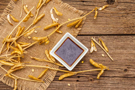 Ripe dry soybeans in pods and dark soy sauce. Cultivated organic agricultural crop, traditional healthy ingredients in oriental food. Vintage sackcloth, wooden boards background, copy space, top view