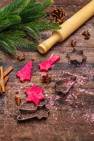 Cooking red ginger cookies. Traditional Christmas pastries. Festive culinary background. Fir tree, spices, cookie cutters, raw dough, rolling pin, wooden boards, close up