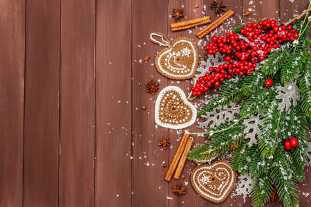 Christmas background. New Year fir tree, dog rose, fresh leaves, crocheted ginger cookies hearts, spices and artificial snow. Wooden boards backdrop, copy space, top view