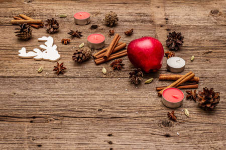 Spirit Christmas background. Apple, candles, spices, deer, cones. Nature New Year decorations, vintage wooden boards, copy space