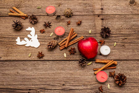 Spirit Christmas background. Apple, candles, spices, deer, cones. Nature New Year decorations, vintage wooden boards, copy space, top view