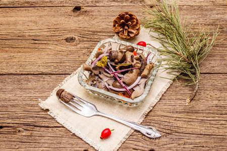Pieczarki marynowane lub sfermentowane. Tradycyjna przekąska świąteczna. Sztućce świąteczne na Nowy Rok. Sosna zimozielona, szyszka, przyprawy, kryształowa płyta. Drewniane deski tło, kopia przestrzeń
