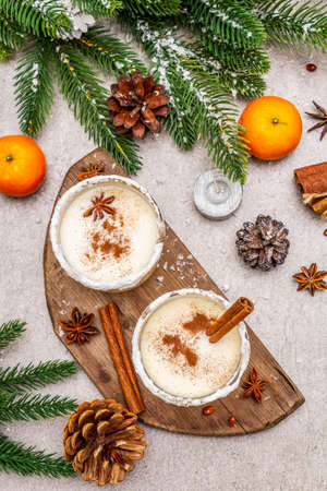 Eggnog with cinnamon and nutmeg for Christmas and winter holidays. Homemade beverage in glasses with spicy rim. Tangerines, candles, gift. Stone concrete background, top view, close up 写真素材