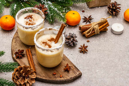 Eggnog with cinnamon and nutmeg for Christmas and winter holidays. Homemade beverage in glasses with spicy rim. Tangerines, candles, gift. Stone concrete background, close up