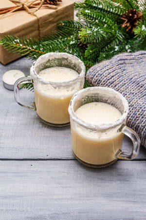 Eggnog cocktail in two glasses mug arranged with christmas decoration on light wooden table. Evergreen fir tree branch, gift, cozy jersey, artificial snow, copy space, close up