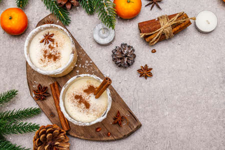 Eggnog with cinnamon and nutmeg for Christmas and winter holidays. Homemade beverage in glasses with spicy rim. Tangerines, candles, gift. Stone concrete background, copy space, top view