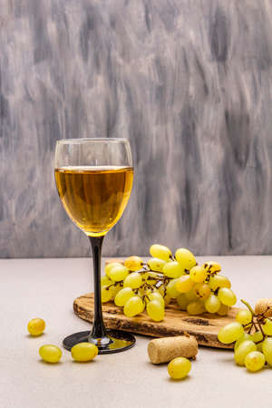 Wine glass, fresh grapes and corks on wooden chopping board. Wine bar, winery, wine tasting concept. Stone concrete background, copy space 版權商用圖片