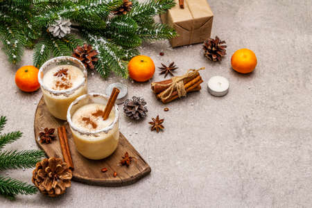 Eggnog with cinnamon and nutmeg for Christmas and winter holidays. Homemade beverage in glasses with spicy rim. Tangerines, candles, gift. Stone concrete background, copy space 写真素材