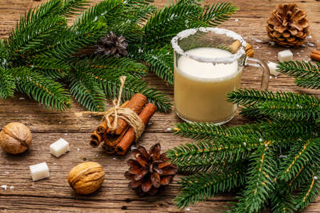 Christmas eggnog liqueur or cola de mono cocktail. Classical winter drink in glass mug, xmas decorations. Evergreen branches, cinnamon, walnuts, sugar. Old wooden background, close up