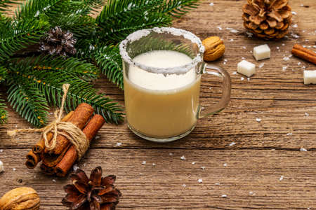 Christmas eggnog liqueur or cola de mono cocktail. Classical winter drink in glass mug, xmas decorations. Evergreen branches, cinnamon, walnuts, sugar. Old wooden background, copy space 写真素材