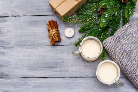 Eggnog cocktail in two glasses mug arranged with christmas decoration on light wooden table. Evergreen fir tree branch, gift, cozy jersey, artificial snow, copy space, top view 写真素材