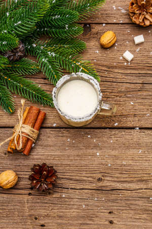 Christmas eggnog liqueur or cola de mono cocktail. Classical winter drink in glass mug, xmas decorations. Evergreen branches, cinnamon, walnuts, sugar. Old wooden background, copy space, top view