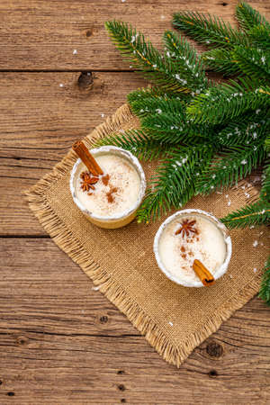 Eggnog cocktail in two glasses arranged with christmas decoration on old wooden table. Evergreen fir tree branch, artificial snow, sackcloth napkin, copy space, top view 写真素材