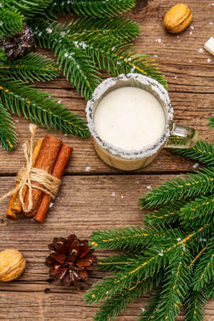 Christmas eggnog liqueur or cola de mono cocktail. Classical winter drink in glass mug, xmas decorations. Evergreen branches, cinnamon, walnuts, sugar. Old wooden background, top view, close up 写真素材
