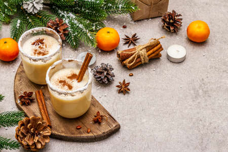 Eggnog with cinnamon and nutmeg for Christmas and winter holidays. Homemade beverage in glasses with spicy rim. Tangerines, candles, gift. Stone concrete background, copy space, close up 写真素材