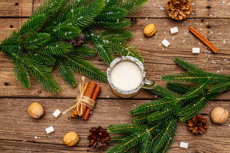 Christmas eggnog liqueur or cola de mono cocktail. Classical winter drink in glass mug, xmas decorations. Evergreen branches, cinnamon, walnuts, sugar. Old wooden background, top view