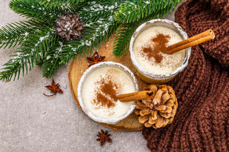 Homemade eggnog with cinnamon in glass. Typical Christmas dessert. Evergreen fir brunch, cones, cozy plaid, artificial snow. Stone concrete background, top view, close up