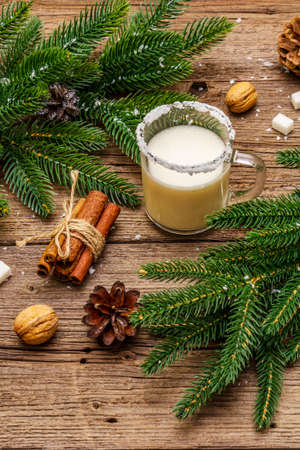 Christmas eggnog liqueur or cola de mono cocktail. Classical winter drink in glass mug, xmas decorations. Evergreen branches, cinnamon, walnuts, sugar. Old wooden background 写真素材