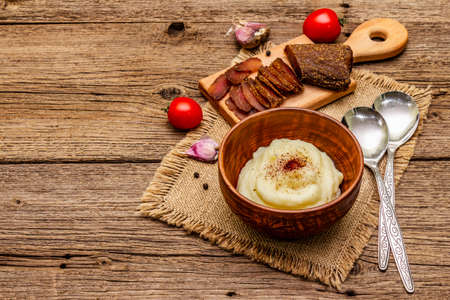 Homemade Thanksgiving garlic mashed potatoes with fresh tomatoes and pastrami. Sackcloth napkin, spoons, old wooden boards background, copy space Stock Photo
