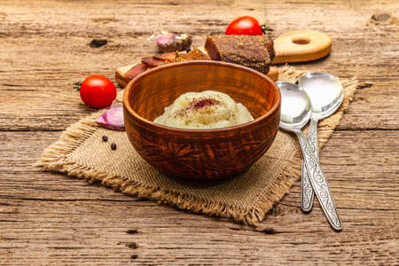Homemade Thanksgiving garlic mashed potatoes with fresh tomatoes and pastrami. Sackcloth napkin, spoons, old wooden boards background, close up Stock Photo