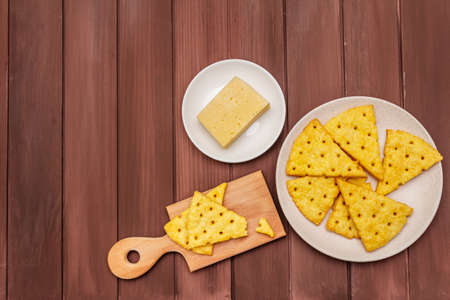 Cheese crackers, salty snack concept. Cookies, piece of cheese, cutting board. Wooden planks background, copy space, top view