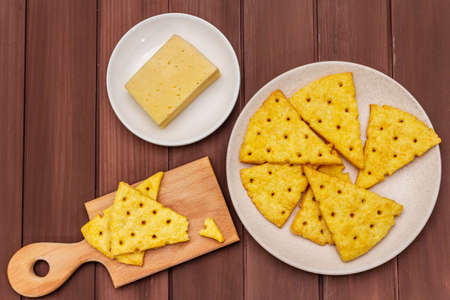 Cheese crackers, salty snack concept. Cookies, piece of cheese, cutting board. Wooden planks background, top view, close up