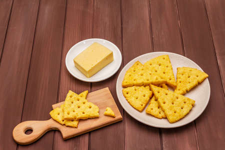 Cheese crackers, salty snack concept. Cookies, piece of cheese, cutting board. Wooden planks background, copy space